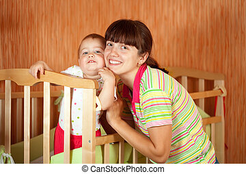 Happy mother with baby in crib
