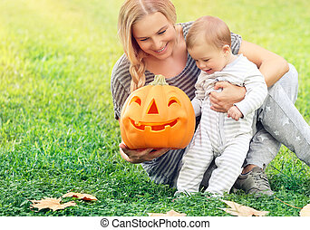 Happy mother with baby in Halloween holiday
