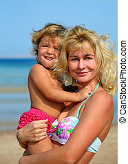 Happy mother with baby on beach