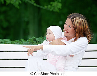 happy mother with baby on the bench - outdoor picture of...