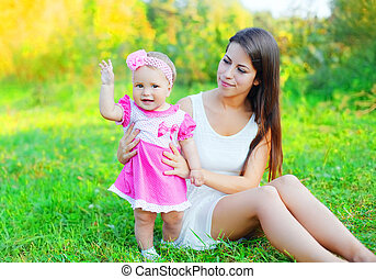 Happy mother with baby together sitting on grass in summer day