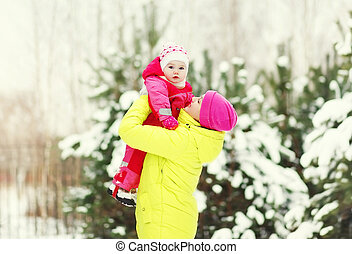 Happy mother with baby walking in snowy winter day