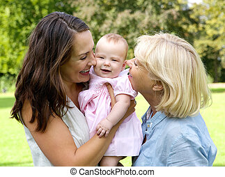 Happy mother with child and grandmother outdoors