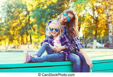 Happy mother with child daughter having fun together in the park