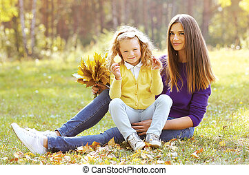 Happy mother with child having fun in autumn park outdoors