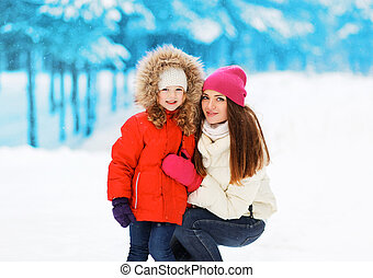 Happy mother with child in winter snowy day
