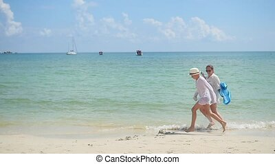 Happy mother with child run on the sandy beach. Tropical island on a hot day