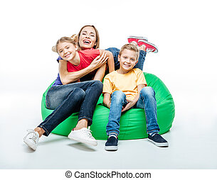 Happy mother with children in sack-chair