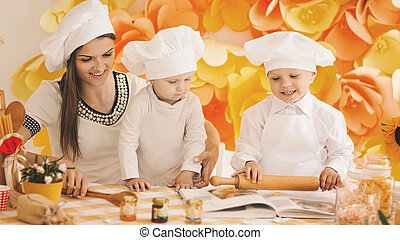happy mother with children preparing dinner in the kitchen