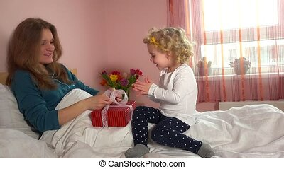 Happy mother with cute little daughter unboxing gift box sitting on bed