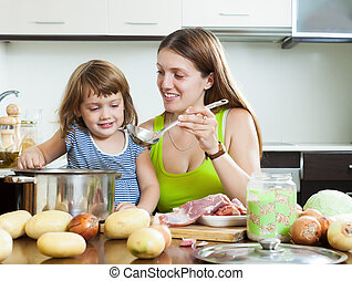 Happy mother with daughter cooking together