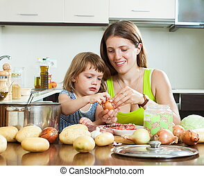 Happy mother with daughter cooking with groats at home