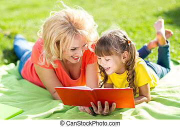 Happy mother with daughter in park reading book
