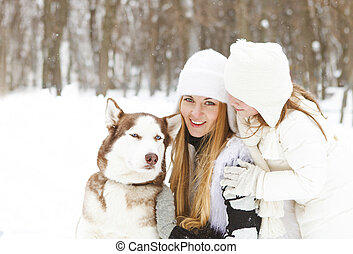 Happy mother with daughter in the winter park with huskies dog