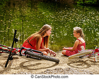 Happy mother with daughter rides bicycle and sitting on beach.