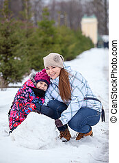 Happy mother with daughter sitting in snow with snowball at winter park