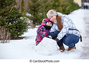 Happy mother with daughter sitting together in snow at winter park