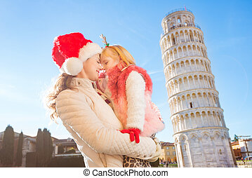 Happy mother with daughter spending Christmas in Pisa, Italy