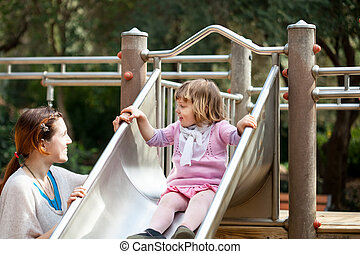 happy mother with  girl on slide