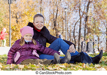 mother with girl sitting in autumn park