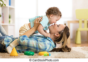Happy mother with her baby having fun pastime on the carpet in nursery