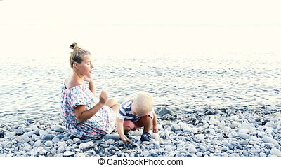 Happy mother with her baby on the beach