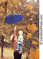 Happy mother with her child holds an umbrella in an autumn park