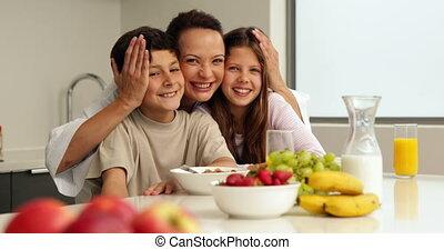 Happy mother with her children having breakfast