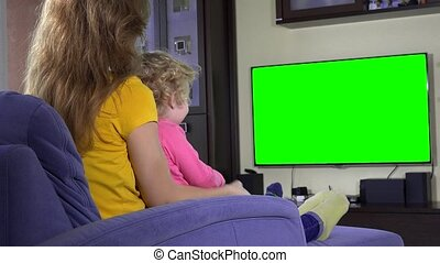 Happy mother with her cute daughter girl watching tv funny...