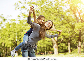 happy mother with her daughter in the park on a sunny day