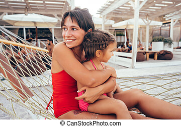 happy mother with her daughter lying in a hammock