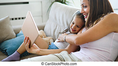 Happy mother with her daughter using digital tablet