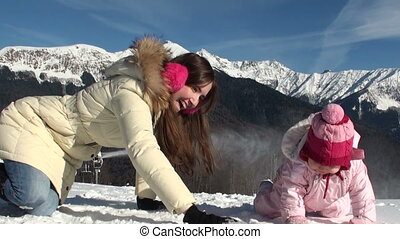 Happy mother with her smiling daughter sculpt snowballs. in the mountains on a sunny day