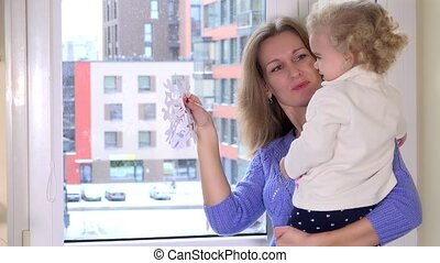 Happy mother with her toddler daughter girl stick paper snow flakes on window