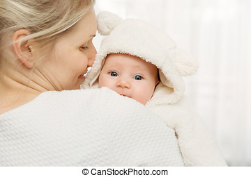 happy mother with infant baby girl dressed in white fluffy costume