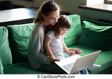 Happy mother with kid daughter having fun online with laptop