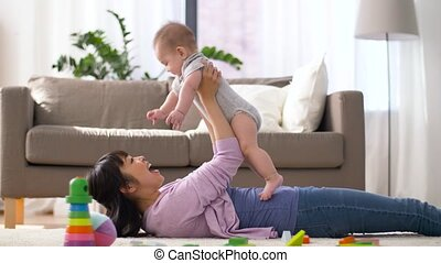 happy mother with little baby boy playing at home
