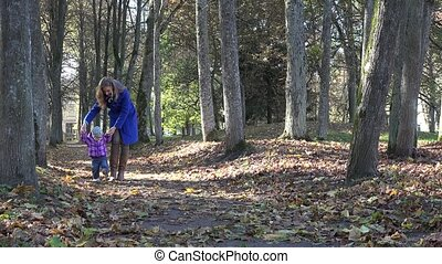 happy mother with little baby girl having fun in autumn park. 4K