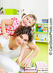 Happy mother with little daughter at home