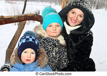 Happy mother with son, daughter smile in winter day during snowfall, focus on girl