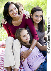 Happy mother with three beautiful children sitting together