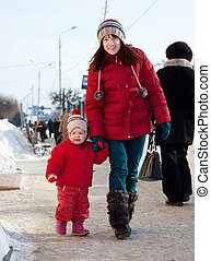 mother with toddler in winter street