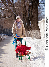 mother with toddler on sled in winter