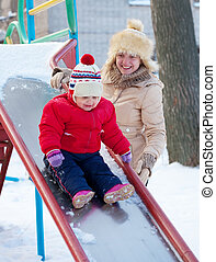 happy mother with  toddler playing on slide