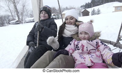 Happy Mother with two children on large swing in winter, slowmotion