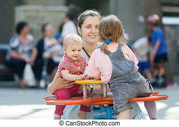 Happy mother with  two children on swing