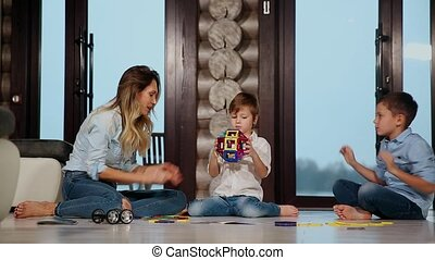 Happy mother with two children sitting on the floor of his country house spending time together collecting children's designer. Living room with panoramic Windows.