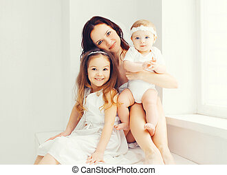 Happy mother with two her daughters children at home in white room sitting together near window