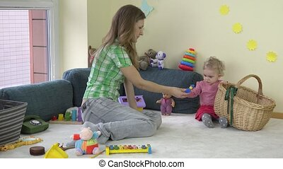 Happy mother woman with adorable toddler daughter girl put toys in basket