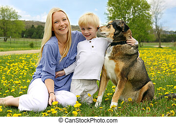 Happy Mother, Young Child, and Dog in Meadow